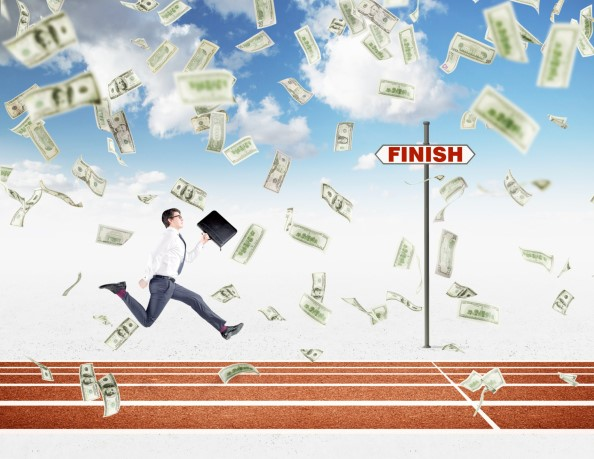 Businessman running on track, money falling from sky