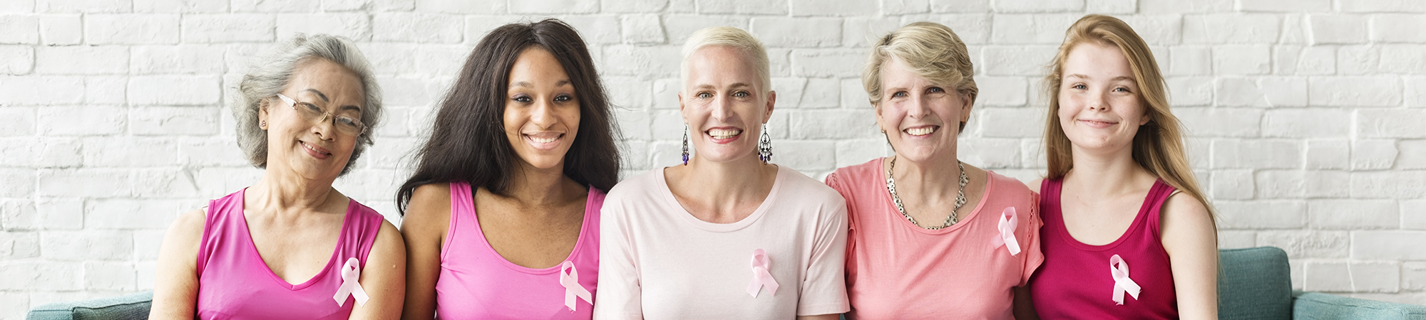 Group of 5 smiling women wearing breast cancer awareness ribbons