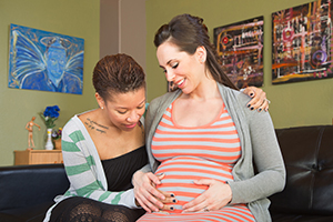 Woman looking at pregnant partner's stomach