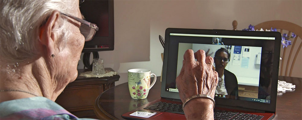 Elderly woman talking with provider via computer