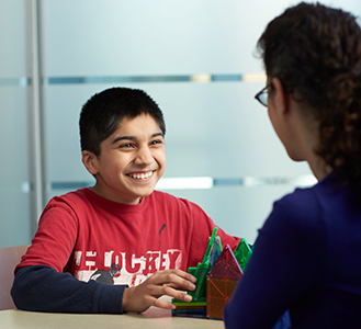 Boy smiling while talking with a provider
