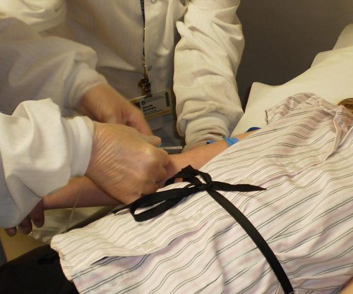 Phlebotomist quickly poking a patient with a butterfly needle