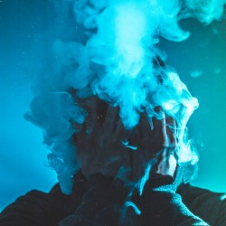Man's face lost in a cloud of vape smoke.
