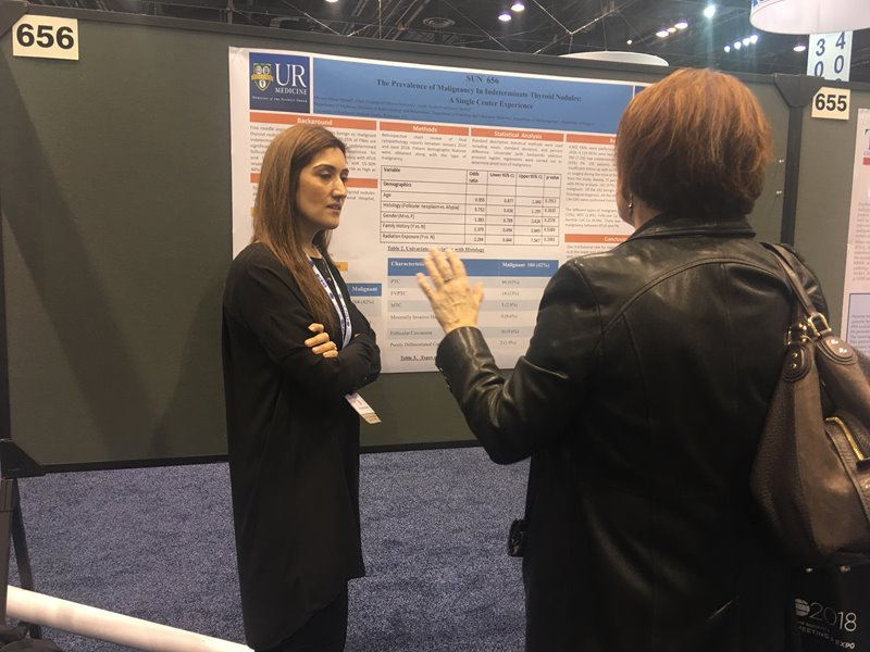 Dr. Miriam Ahmad discussing poster with guest
