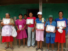 Women health volunteers display certificates after completion of domestic violence training.