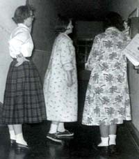 Students, Diane Blixt, Barb Mitchell and Gwen Houssian, in line to use the dorm telephone