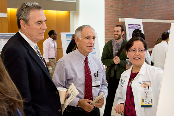 Katia Bravo-Jaimes, MD discusses her poster with Drs. Paul Levy and Mark Berliant