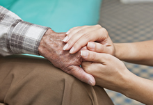 Woman holding hand of elderly man
