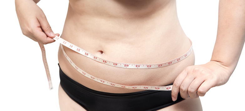 Woman with measuring tape around stomach