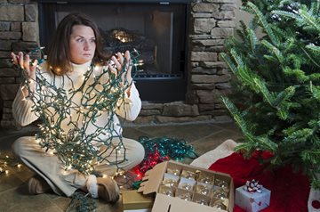 woman holding a tangle of Christmas tree lights