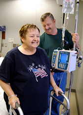 woman walking with husband in hospital room
