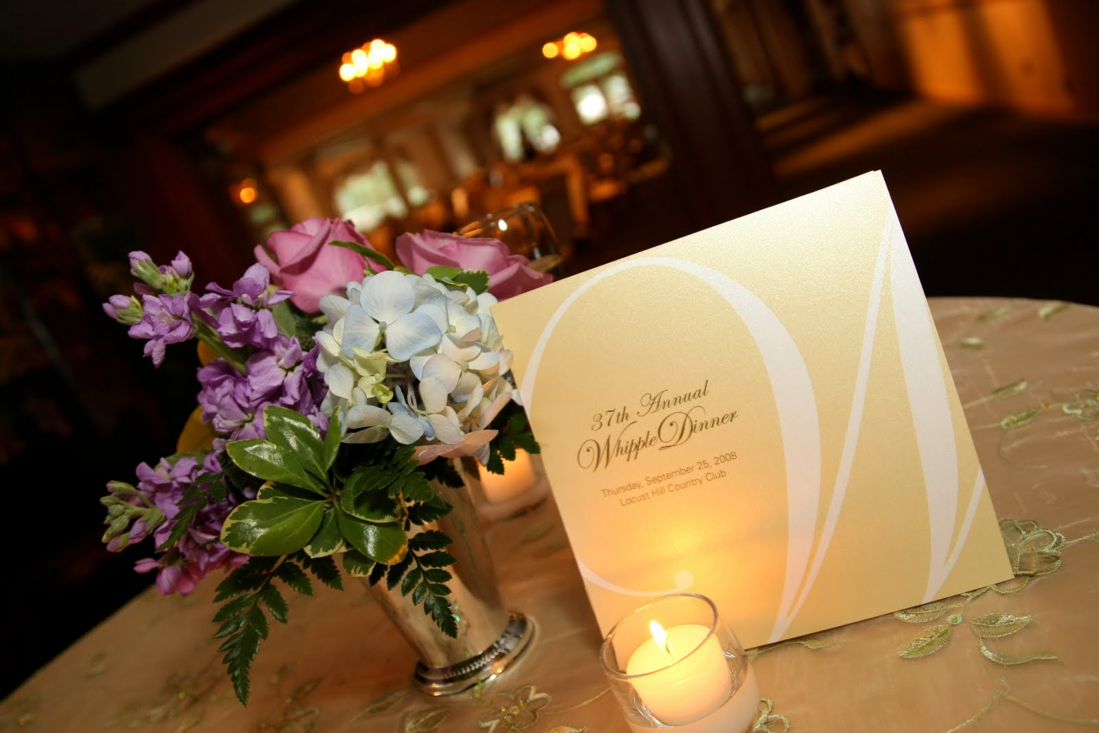 invite on table next to flowers. Invite illuminated by candle