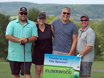 First place mixed team holding sign: Thanks to our Title Sponsor - Elderwood