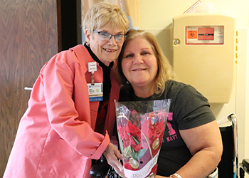 Rose poses for a picture with a patient while making annual holiday poinsettia deliveries.