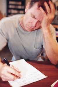 Photo of man struggling with problems on a paper