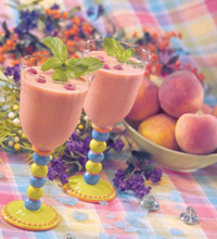 Colorful table setting with two peach melba smoothies