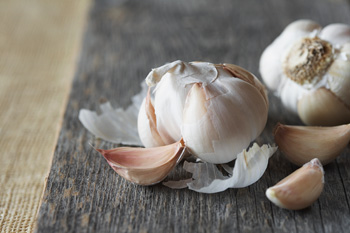 Garlic cloves sitting on a wooden surface.