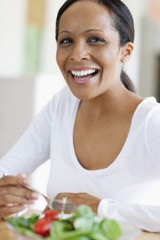 Photo of a woman looking at the camera and smiling. She is eating a green salad.