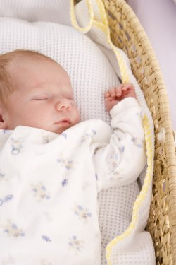 Baby sleeping on his back in a bassinet