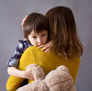 Young child in his mother's arms with a sad look on his face.