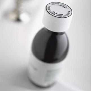 Close up image of a bottle of cough medicine.