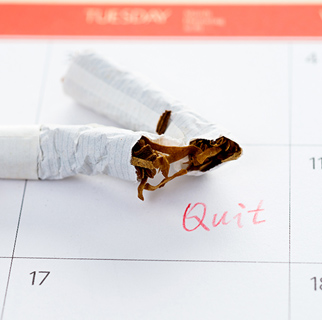 """close up image of a broken cigarette on top of a calendar date square with the word """"quit"""" written in the square."""
