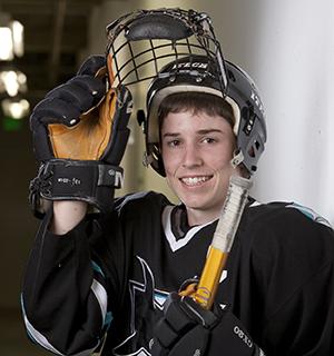 Teenage boy wearing protective gear for hockey.
