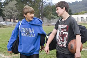 Two teen boys with sports gear talking outside.
