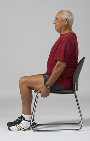 Man sitting in chair, holding the seat