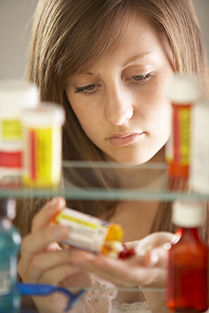 Teenage girl pouring out pills, view through medicine cabinet.