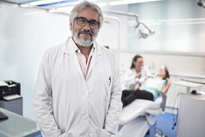 Male dentist standing and smiling in front of an exam chair