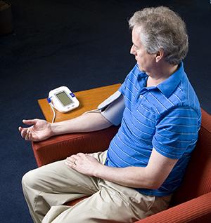 Man taking blood pressure at home.