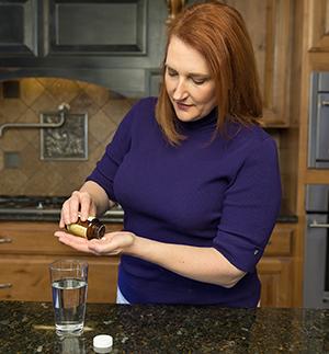 Woman taking pills in kitchen.