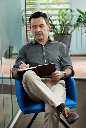Man sitting in chair while writing in notebook.