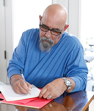 Man sitting at table, writing.