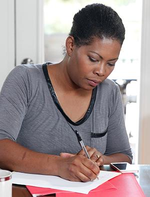 Woman sitting at table, writing.