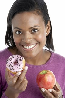 young woman choosing between an apple and a banana the every other day diet