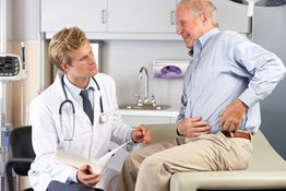 Doctor examining elderly patient with hip pain
