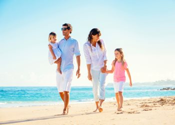 family walking on tropical beach