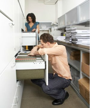 Man and woman search for files in a large laboratory filing cabinet