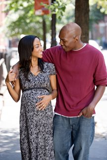 pregnant woman walking outside with partner