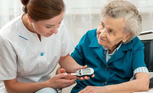 Nurse with patient using blood sugar detection device