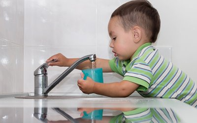 little boy getting a drink of water from a faucet