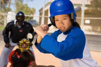 teenage girl at bat in softball game