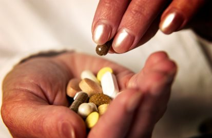 woman's hands holding nutritional supplements
