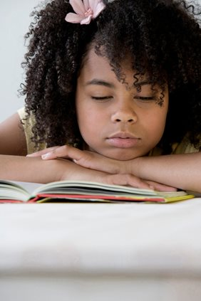 young girl falling asleep reading a book