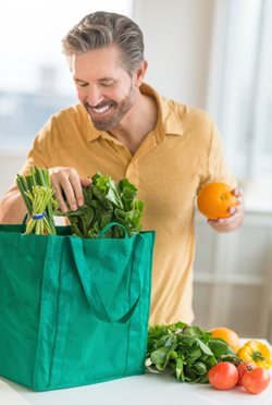 man unpacking grocery bag
