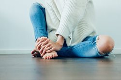 woman sitting on floor with hands on bare feet