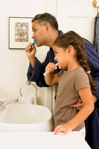 father and daughter brushing teeth