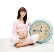 Pregnant woman with large clock